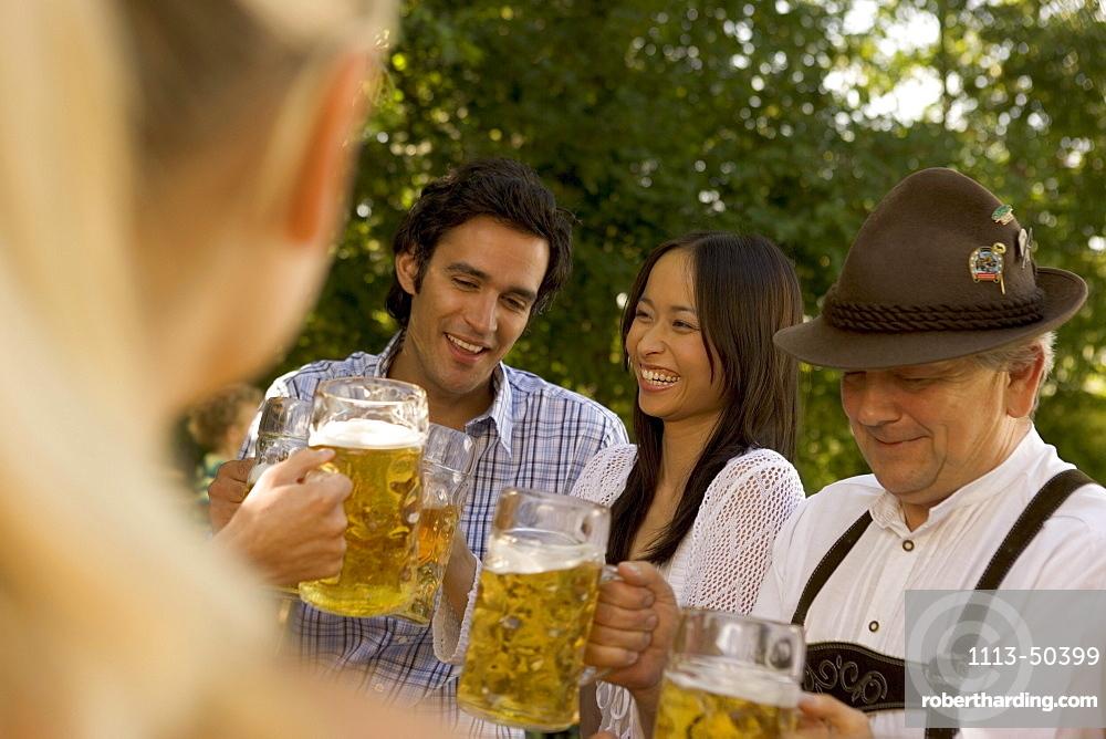 Friends toasting in beergarden, Bavaria, Germany