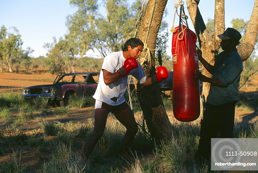 Denny und Paul boxing the sandbag, Fred Brophy's Boxing Troupe, Boulia, Simpson Desert, Australia