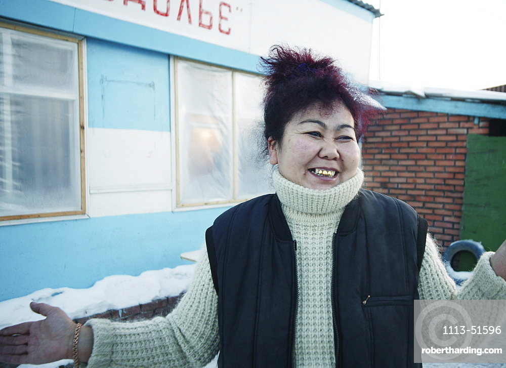 Smiling woman standing in front of a house, Omsk, Siberia