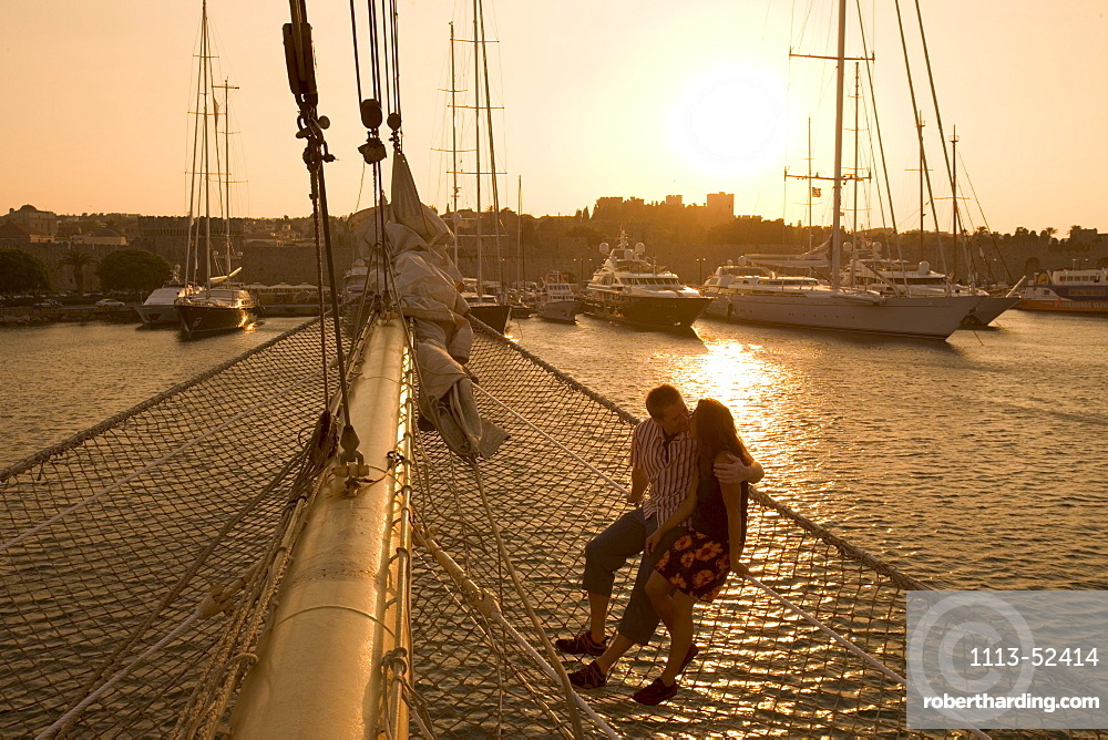 Couple in Bowsprit Net, Star Flyer, sunset over the Rhodes Harbor, Rhodes, Dodecanese Islands, Greece