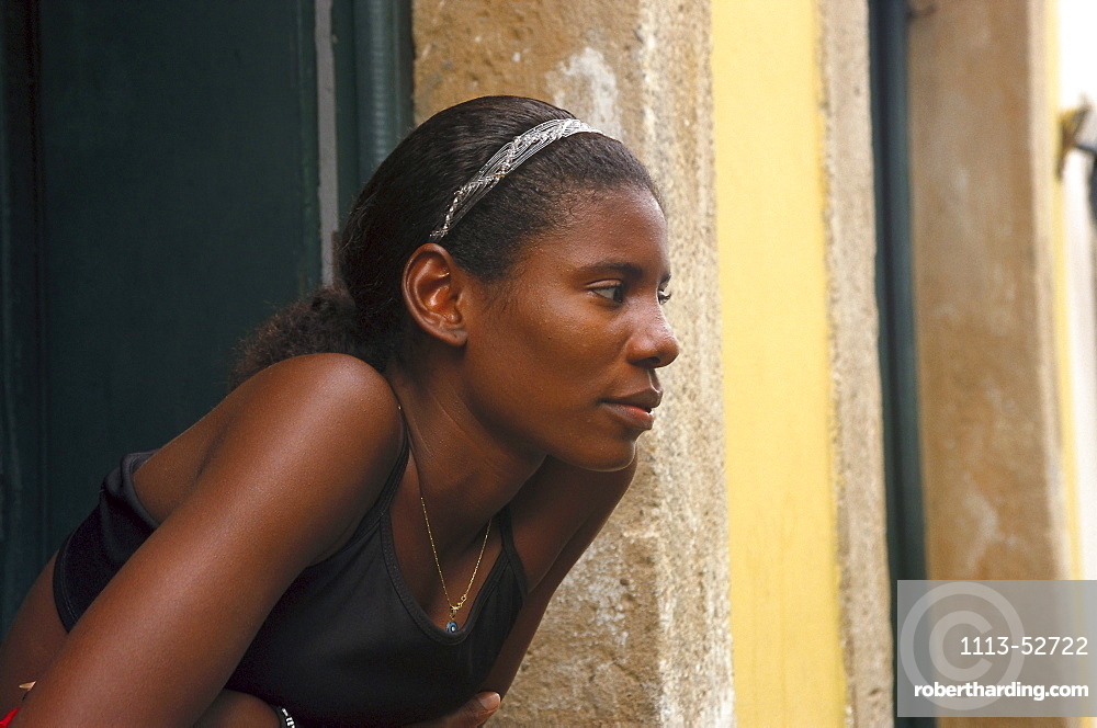 Young woman leaning out of the window, Pelourinho, Salvador da Bahia, Brazil, South America