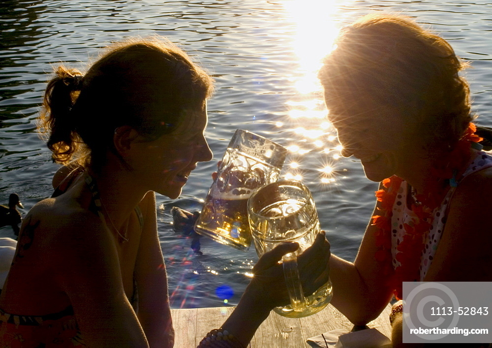 Young women toasting with beer steins, Seehaus Beergarden, English Garden, Munich, Bavaria, Germany
