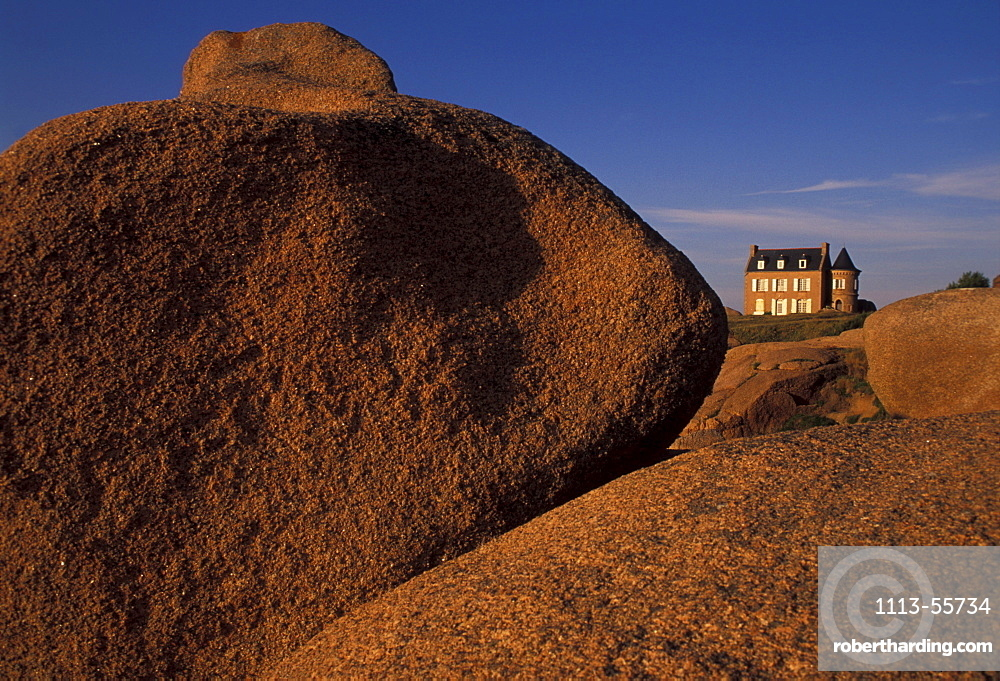House on limestone boulders in the sunlight, Cote de Granit Rose, Brittany, France, Europe