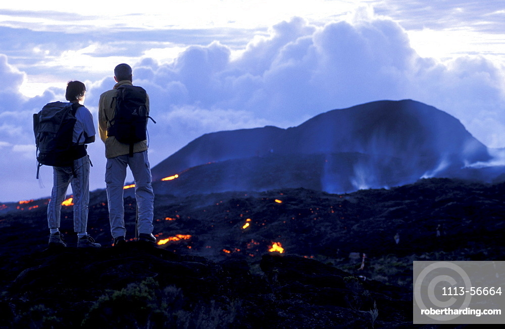 Two people watching glowing lava at Piton Kapor volcano, Ille de la RÈunion, Indian Ocean