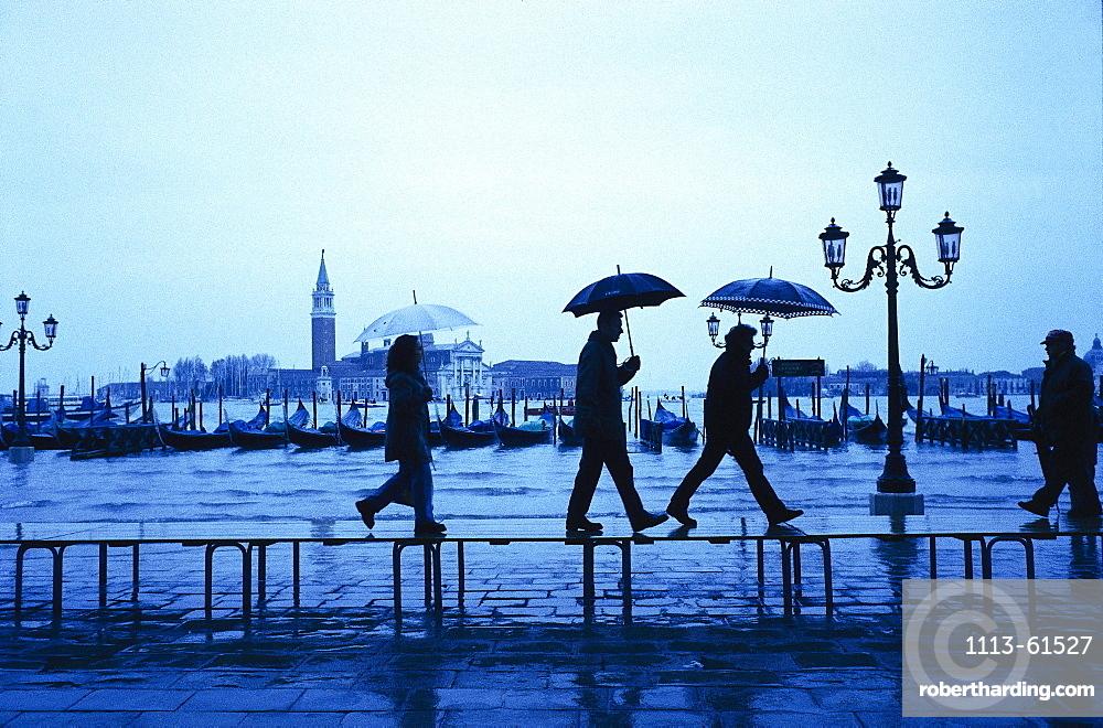 People are walking in the rain over the flooded Gorgio Maggiore in Venice, Italy
