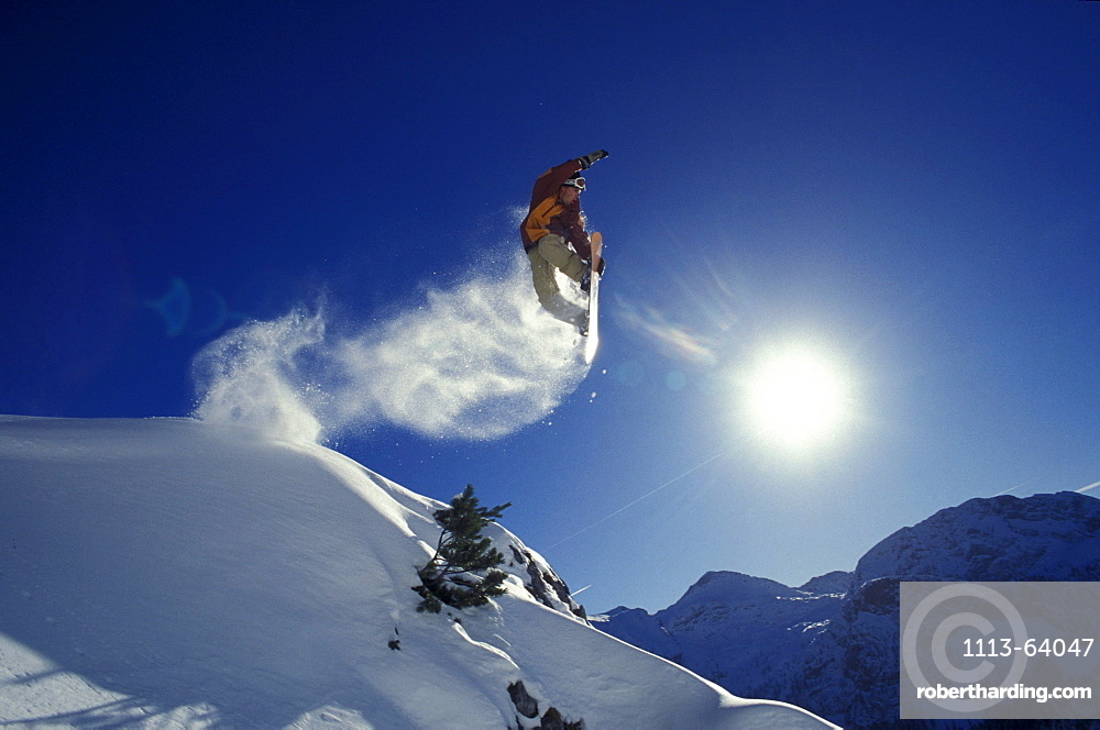A snowboarder during a jump in front of a blue sky
