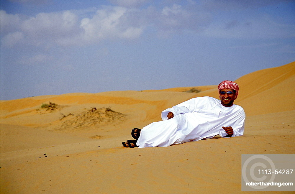 Man lying in the sand at the desert, Sultanat Oman, Middle East, Asia