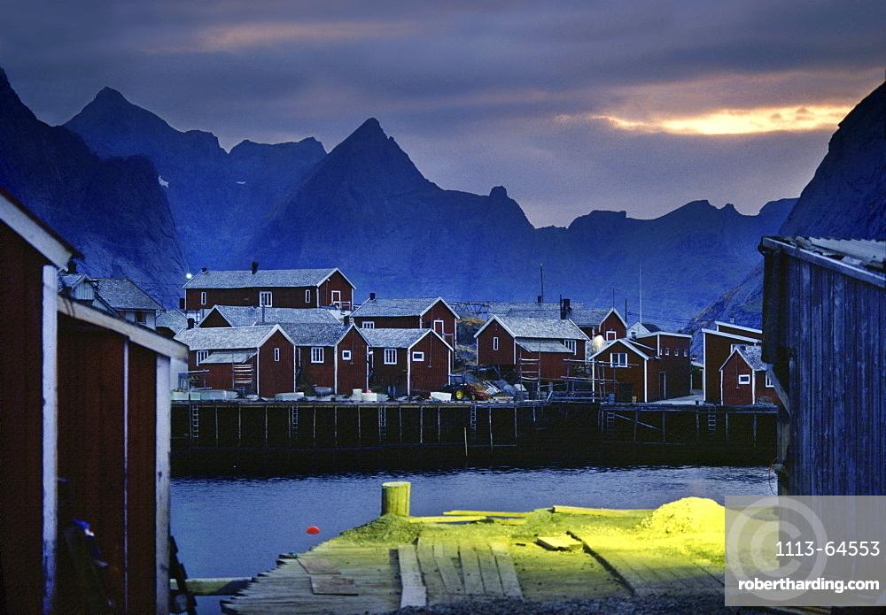 Rorbu huts at fishing village under clouded sky in the evening, Reine, Lofoten Islands, Norway, Scandinavia, Europe