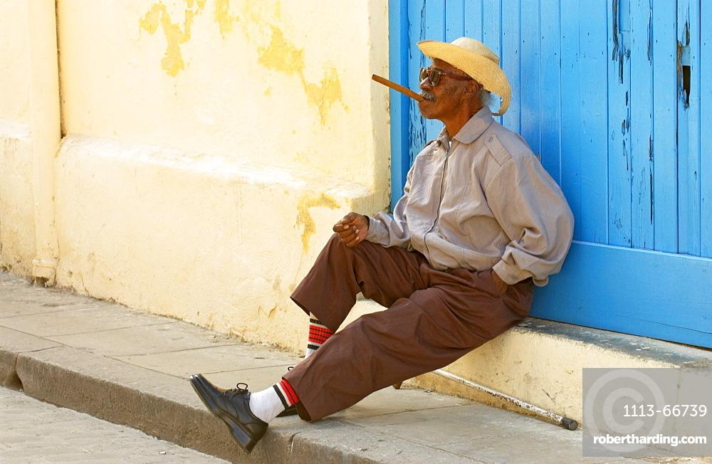 Blind old man sitting in front of a blue gate having a cigar, Havana, Kuba