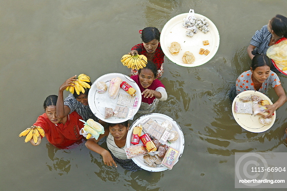 Women vendors standing waist-high in river, carrying fruit, Myanmar