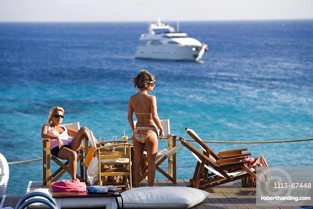 Women in the Goya Beach Bar, the only beach bar with pool, watching to a yacht at sea, Paranga Beach, Mykonos, Greece