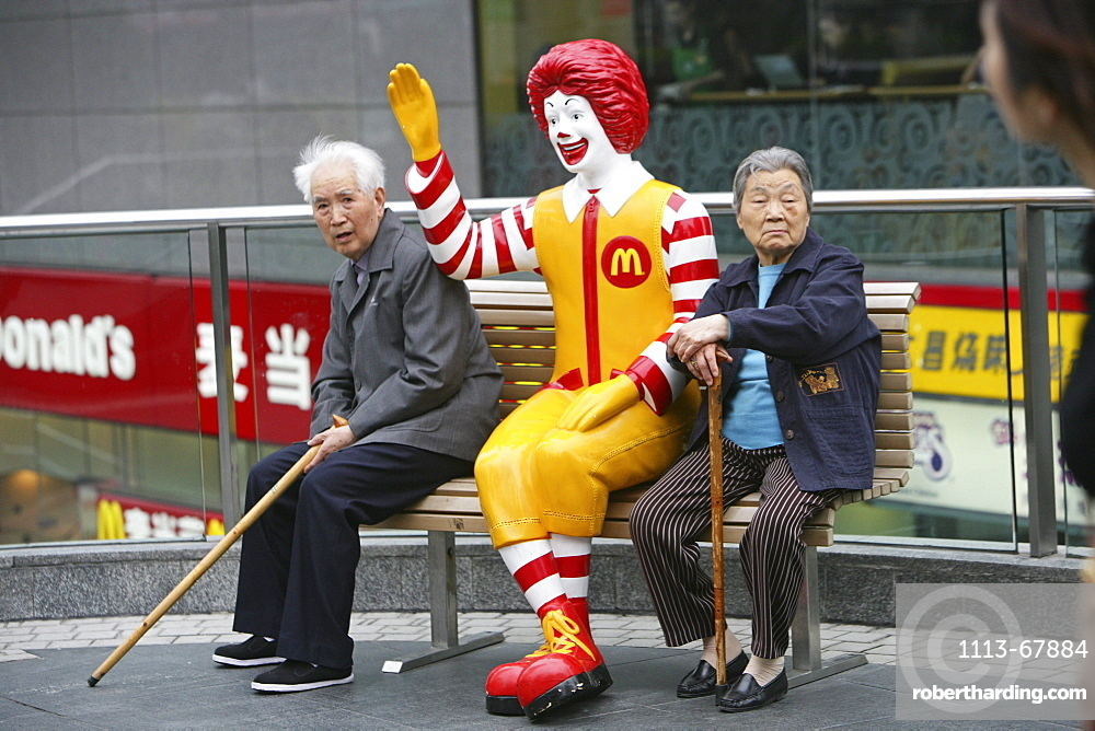 Ronald McDonald figure, pensioners rest on a bench, Fastfood