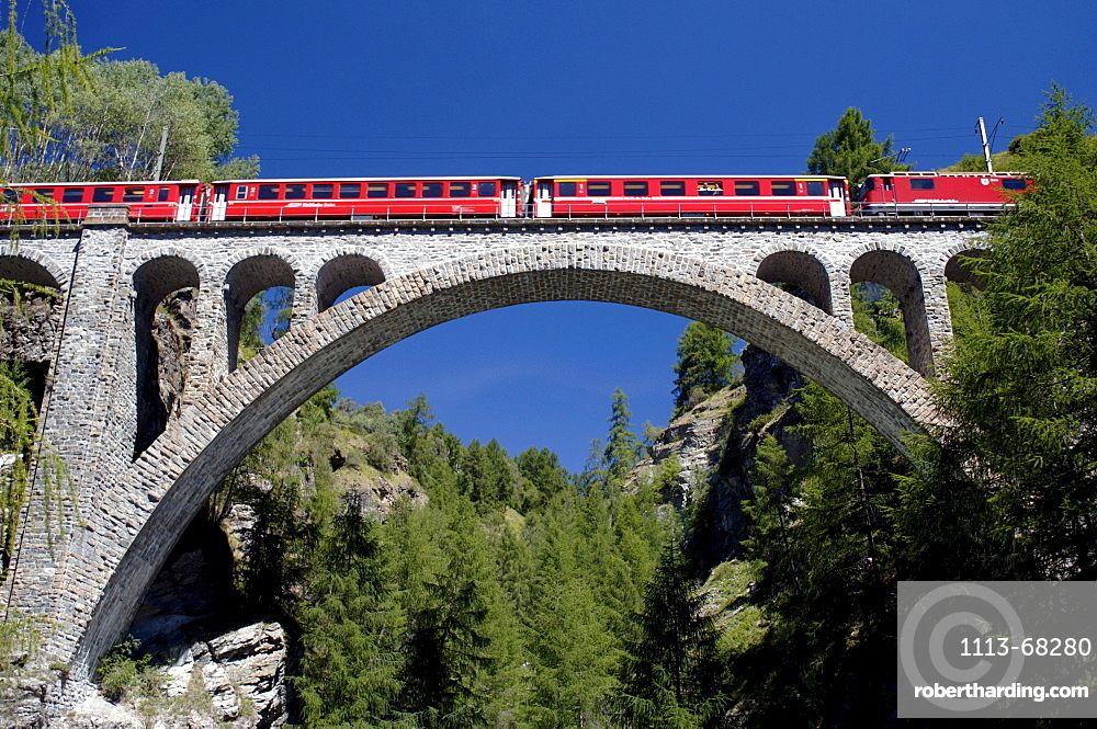 Train crossing a viadukt under blue sky, Guarda, Grisons, Switzerland