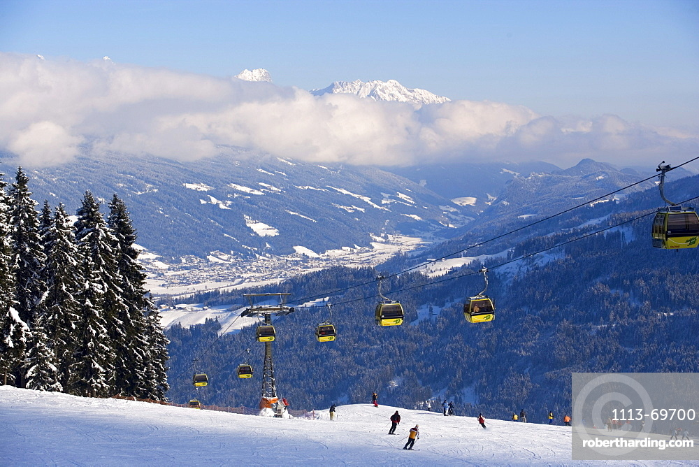 Achter Jet, 8-seated cabin cable car, Austria's 1st mono-cable aerial ropeway, skiers on slope, summit of the Dachsteinregion at horizon, Flachau, Salzburger Land, Austria