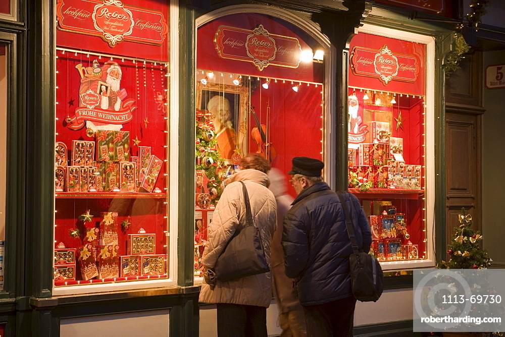 People standing in front of the christmassy decorated shop window of Reber, a shop, where you can buy Mozartkugeln, Old Market, Salzburg, Salzburg, Austria