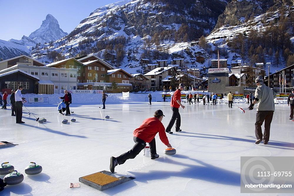 People curling on a rink, Matterhorn in background, Zermatt, Valais, Switzerland