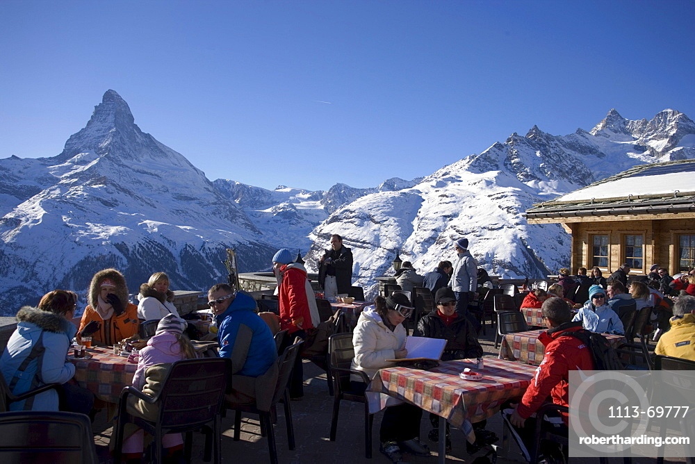People sitting on the terrace of the Restaurant Blauherd with a view to the Matterhorn, Zermatt, Valais, Switzerland (2571 metres above sea level)