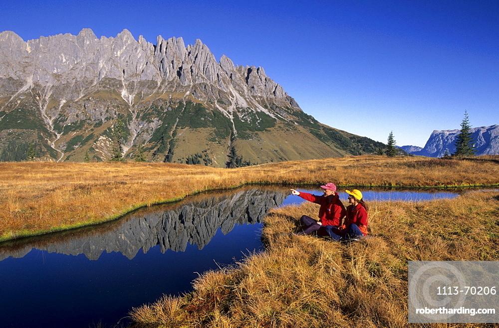 two hikers at lake on Hochkeil, view to Bratschenkopf, Manndlwand, Hochkoenig area, Barchtesgaden range, Salzburg, Austria