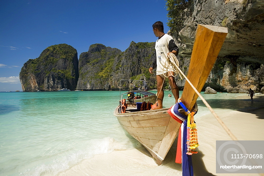 Boatman standing on a long tail boat and holding a rope, Maya Bay, a beautiful scenic lagoon, famous for the Hollywood film