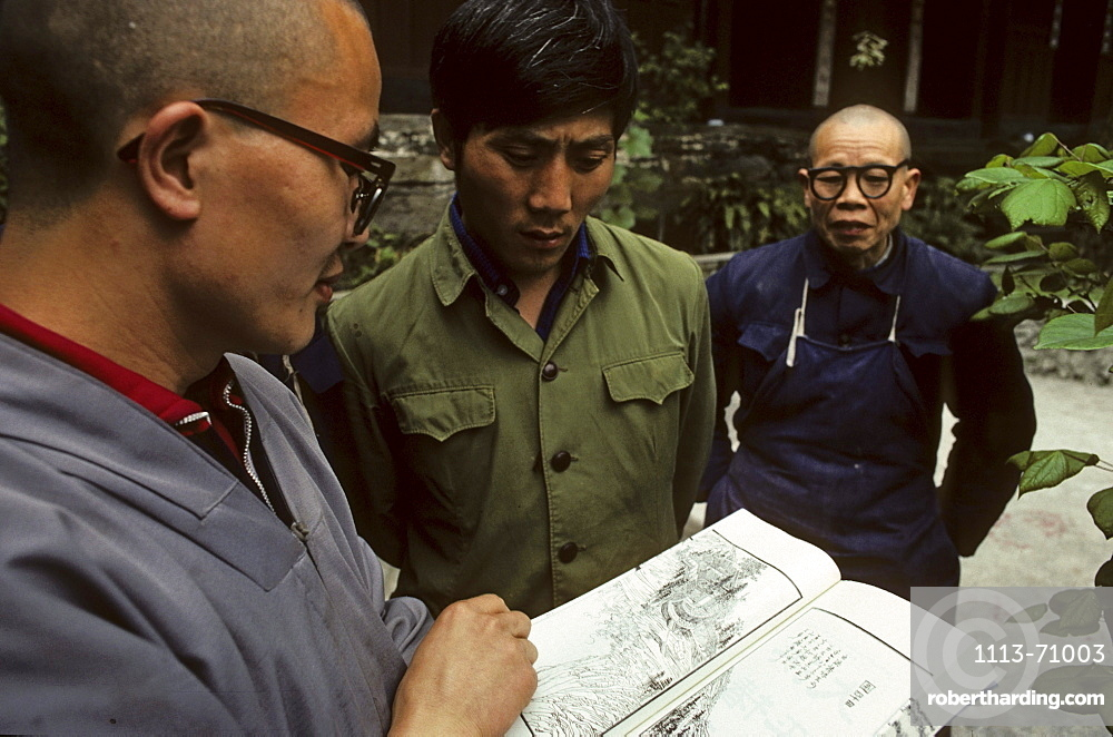 monks study the reprint of a trourist guide from 1932 of Emei Shan, Xixiang Chi monastery and temple, Elephant Bathing Pool, World Heritage Site, UNESCO, China, Asia