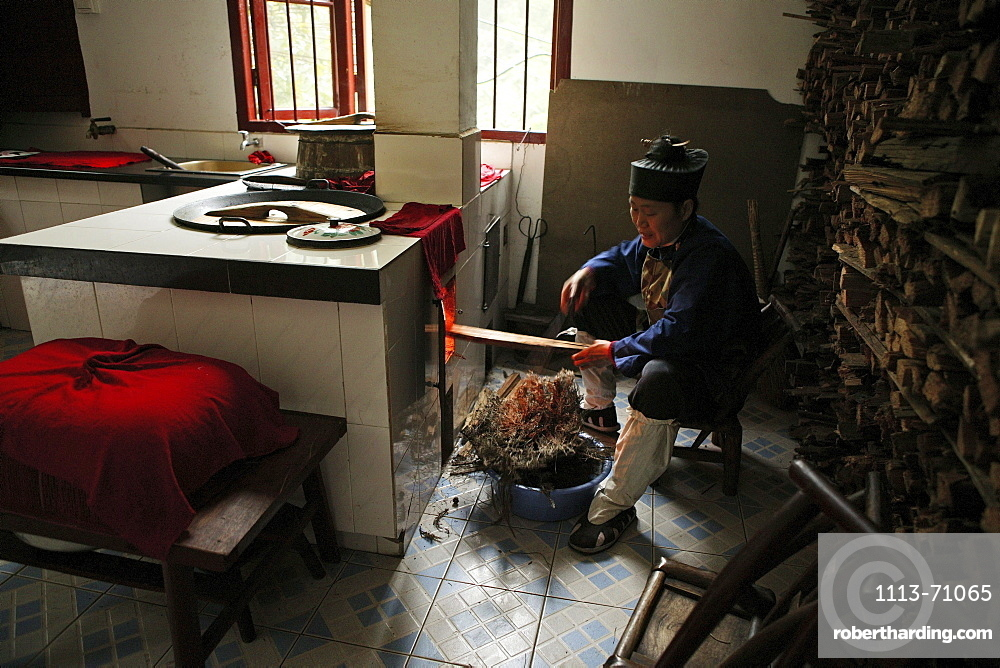 A nun heating up the stove in the kitchen of Nunnery Huanting, Heng Shan South, Hunan province, China, Asia