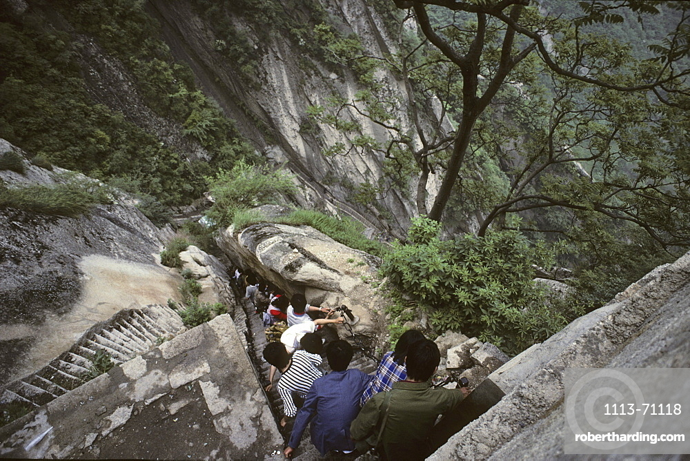 Tourists climbing downwards, stone steps and chains below North Peak, Taoist mountain, Hua Shan, Shaanxi province, Taoist mountain, China, Asia