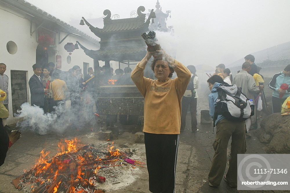 Pilgrims burning incense sticks in front of Longevity monastery, Jiuhua Shan, Anhui province, China, Asia