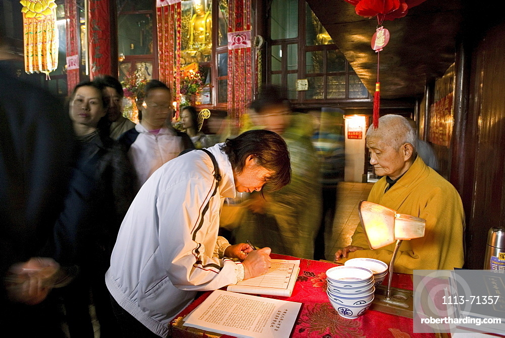 A monk and pilgrims at Longevity temple, Jiuhua Shan, Anhui province, China, Asia