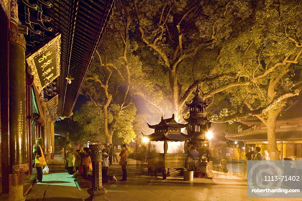 Gingko trees and people standing in front of Puji Si Temple at night, Island of Putuo Shan, Zhejiang Province, China, Asia