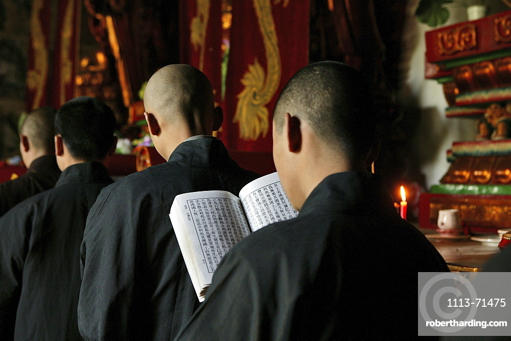 Monks at a prayer service in the Great Buddha Hall, Shaolin Monastery, known for Shaolin boxing, Song Shan, Henan province, China