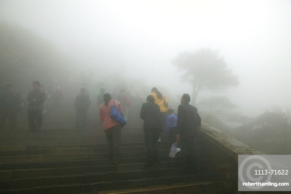 Pilgrims, tourists in rain capes near the entrance to Bixia Si temple in fog, Tai Shan, Shandong province, World Heritage, UNESCO, China