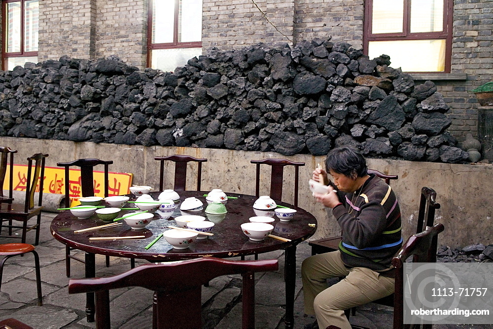 Man eating lunch in the monastery canteen, coal used for cooking in the background, during the birthday celebrations for Wenshu, Mount Wutai, Wutai Shan, Five Terrace Mountain, Buddhist Centre, town of Taihuai, Shanxi province, China