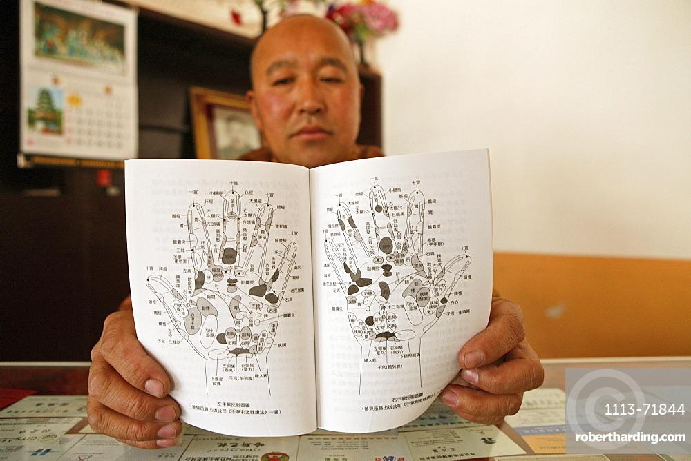 Monk holding diagram for massage, Luohou monastery, Taihuai, Mount Wutai, Wutai Shan, Five Terrace Mountain, Buddhist Centre, town of Taihuai, Shanxi province, China