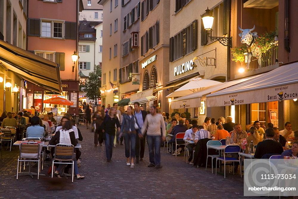 People strolling over Hirschpaltz, passing different pavement cafes and restaurants in the evening (right hand: Restaurant Swiss Chuchi of the Hotel Adler), Niederdorfstrasse, Zurich, Canton Zurich, Switzerland
