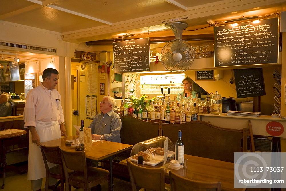 Waiter attending on a guest in the restaurant Weisse Rose (the smallest restaurant of Zurich), Zurich, Canton Zurich, Switzerland