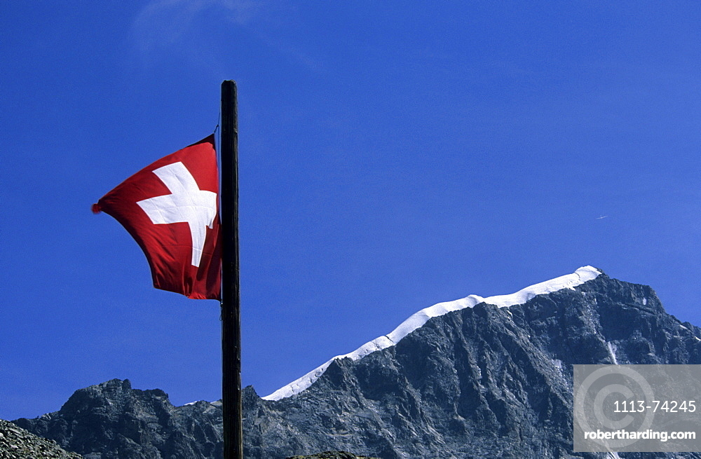 swiss flag with ridge Biancograt, hut Tschiervahuette, Bernina range, Oberengadin, Grisons, Switzerland
