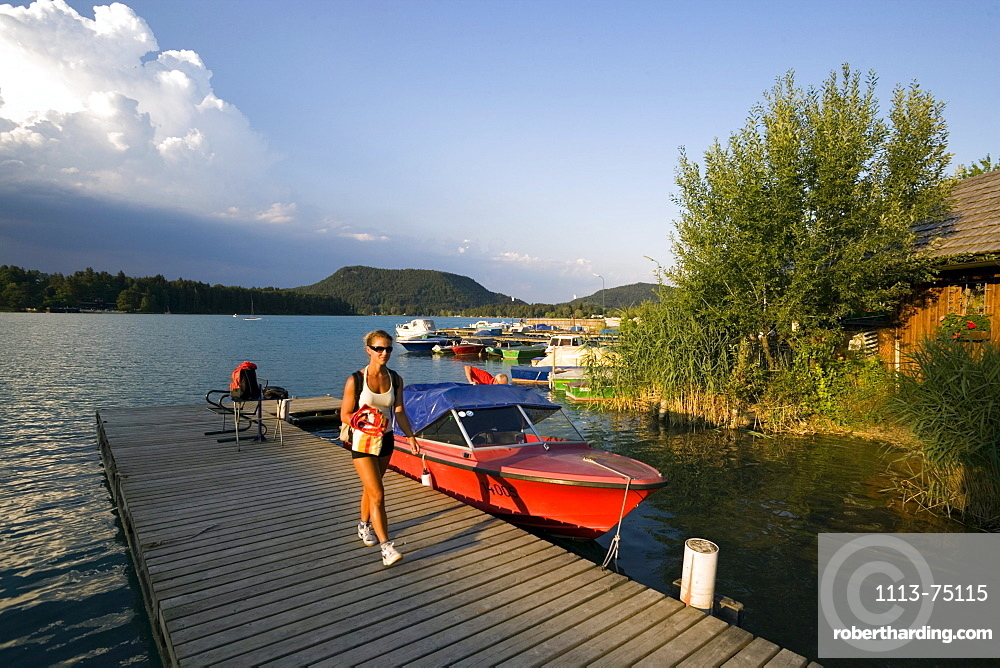 Woman walking over landing stage, Lake Faak, Carinthia, Austria