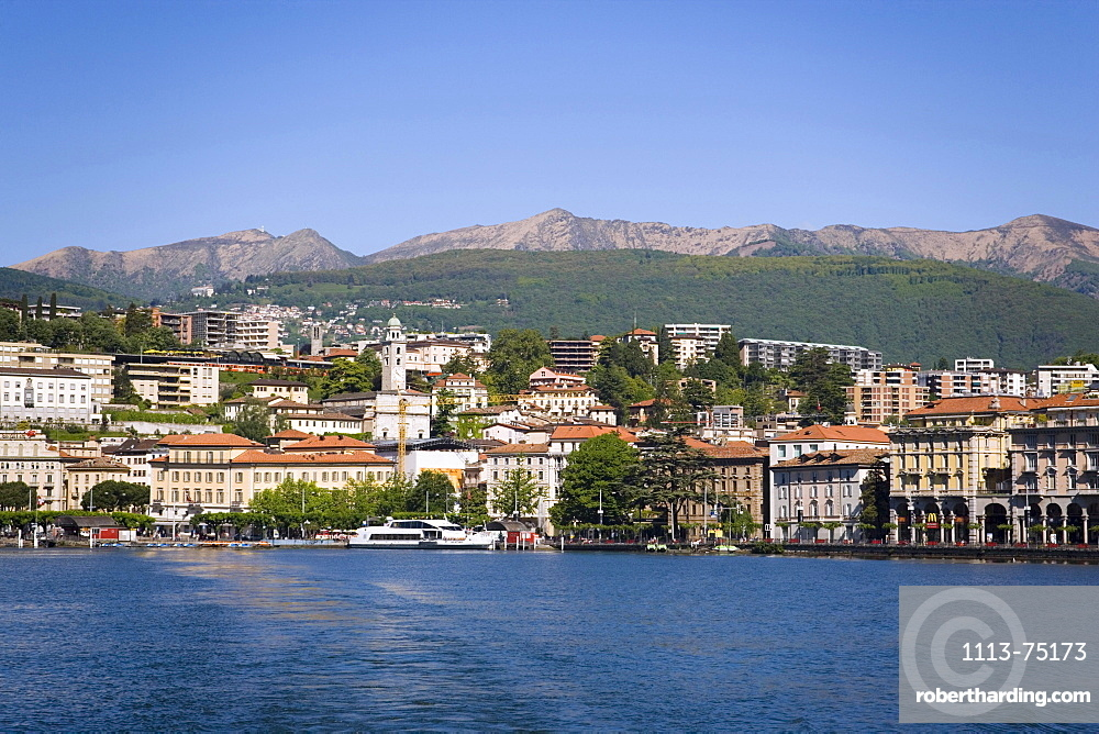 View over Lake Lugano to Lugano with mountains in background, Ticino, Switzerland