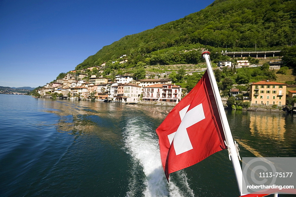 Motorboat on Lake Lugano leaving Gandria, a picturesque village at mountainside of mount Monte Bre, Ticino, Switzerland