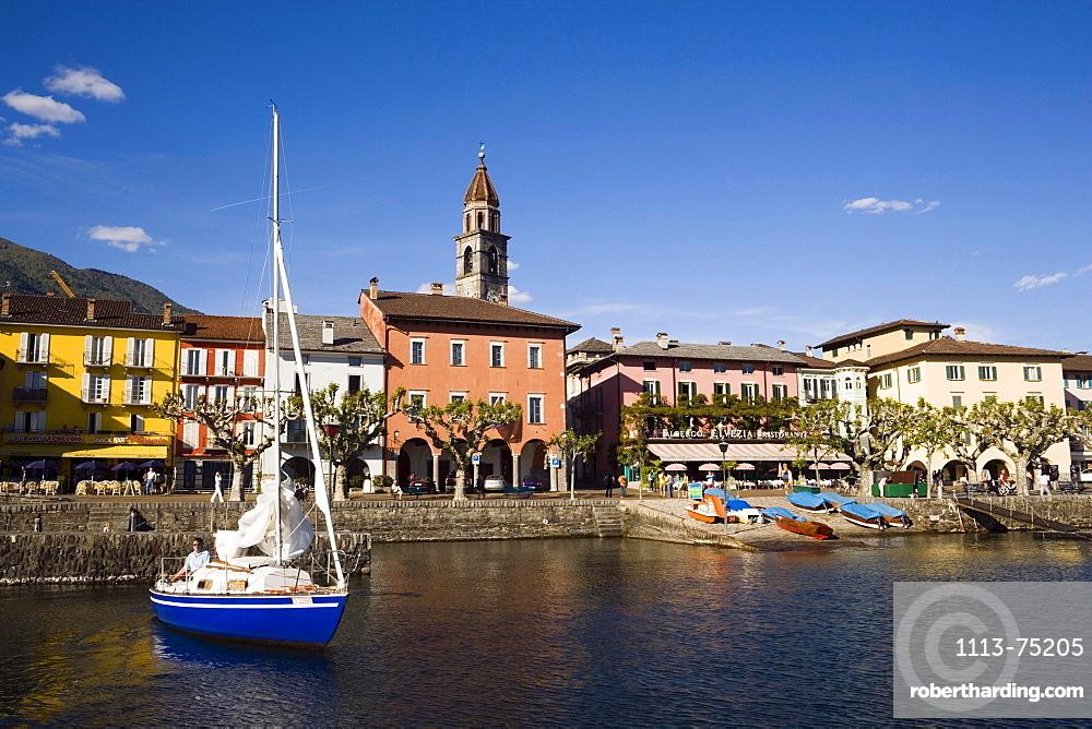 Sailling boat on Lake Maggiore, harbour promenade with spire of church Santi Pietro Paolo in background, Ascona, Ticino, Switzerland