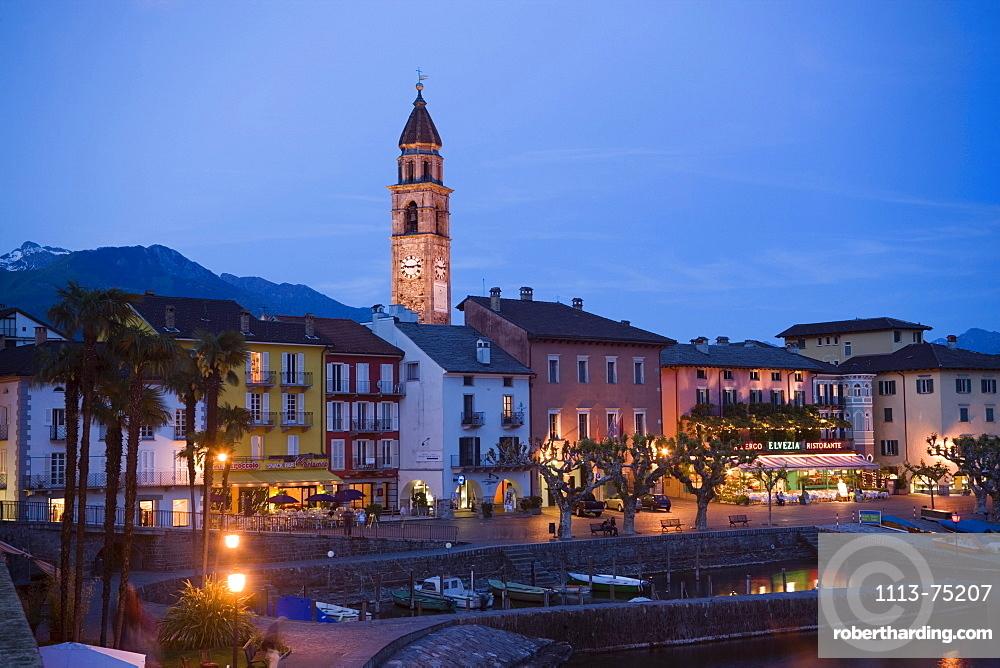 Harbour and harbour promenade with spire of church Santi Pietro Paolo in background in the evening, Ascona, Lake Maggiore, Ticino, Switzerland