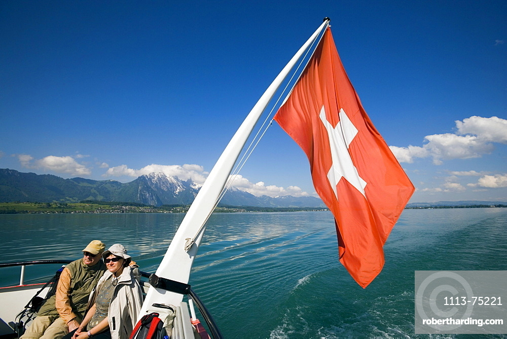 Couple sitting at stern of a ship, swiss flag blowing in the wind, Lake Thun, Bernese Oberland (highlands), Canton of Bern, Switzerland