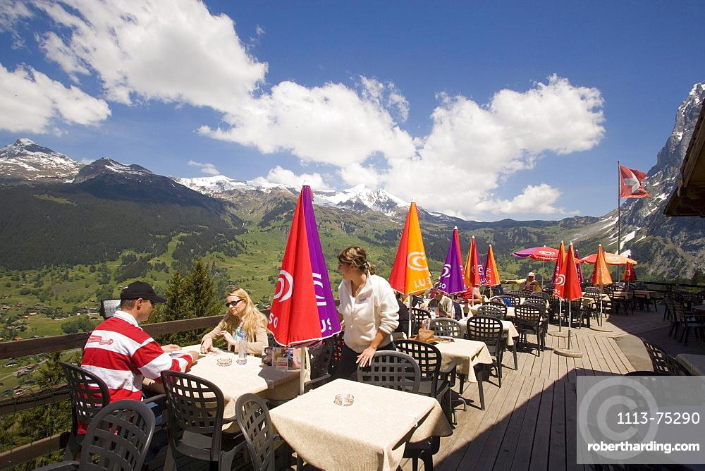 People on sun terrace of the mountain restaurant Pfingstegg, Schreckhorn (4078 m) and Eiger (3970 m) in background, Grindelwald, Bernese Oberland (highlands), Canton of Bern, Switzerland