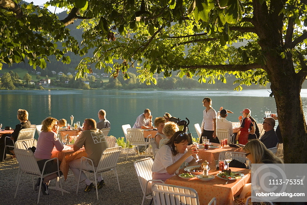 People sitting in the open air area of a restaurant at Lake Fuschl in the evening, Fuschl am See, Salzkammergut, Salzburg, Austria