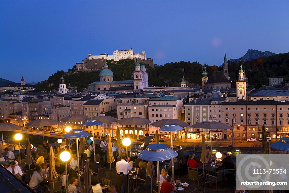 View over illuminated roof deck of restaurant Hotel Stein to old town with Salzburg Cathedral, St. Peter's Archabbey, Franciscan Church, City Hall Tower and Hohensalzburg Fortress, largest, fully-preserved fortress in central Europe, in the evening, Salzburg, Salzburg, Austria, Since 1996 historic centre of the city part of the UNESCO World Heritage Site