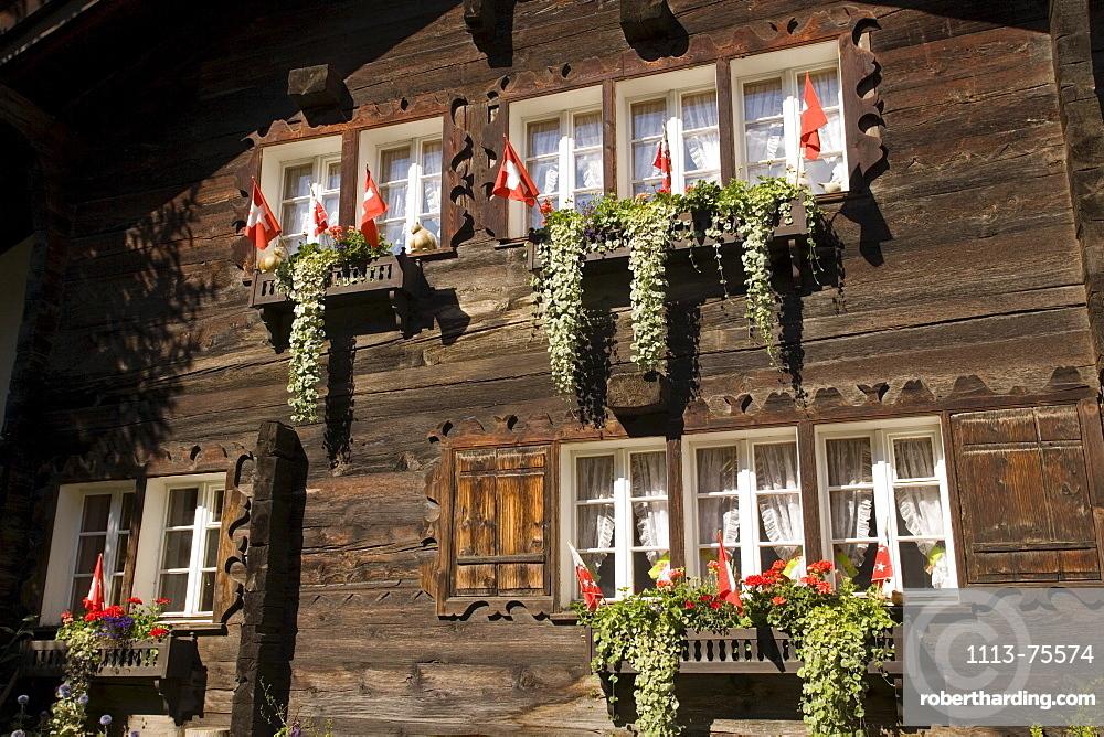With flower boxes and Swiss flags decorated wooden house, Zermatt village, Zermatt, Valais, Switzerland
