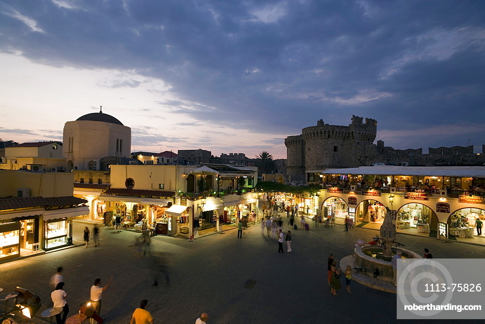View over busy Platia Ippokratou with Thalassini Gate in background in the evening, Rhodes Town, Rhodes, Greece, (Since 1988 part of the UNESCO World Heritage Site)