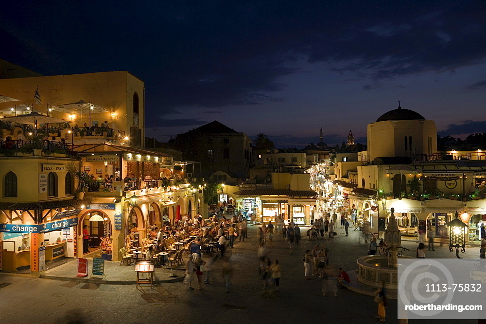 View over Platia Ippokratou with pavement cafes and shops in the evening, Rhodes Town, Rhodes, Greece, (Since 1988 part of the UNESCO World Heritage Site)