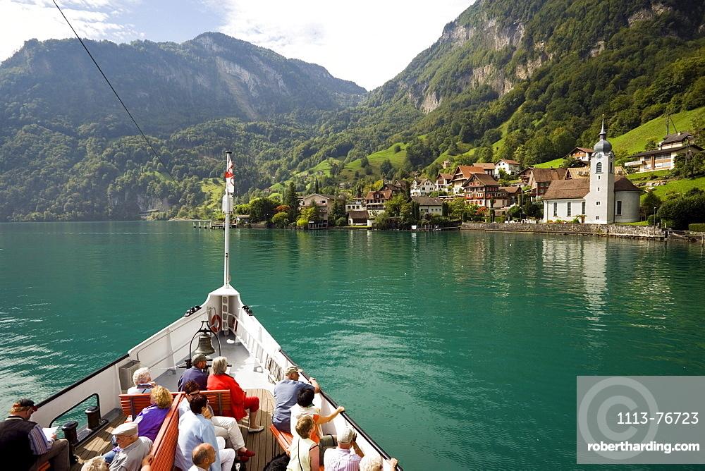 Passengers sitting on deck of a paddle wheel steamer, arriving Bauen, Lake Urnersee, part of Lake Lucerne, Bauen, Canton of Uri, Switzerland