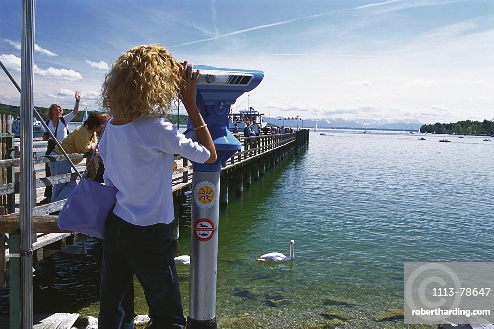 Woman looking through telescope at lake, Lake Starnberg, Bavaria, Germany